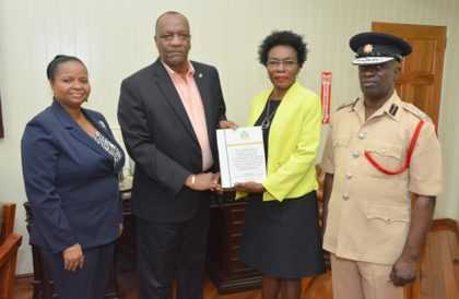 Minister of State, Mr. Joseph Harmon receives the report of the Commission of Inquiry into the deaths of the victims of the Hadfield Street Drop In Centre from Commissioner, Retired Colonel Windee Algernon(centre-right) . Minister of Social Protection, Ms. Volda Lawrence and Acting Chief Fire Officer, Mr. Winston McGregor (right) also received copies of the report.