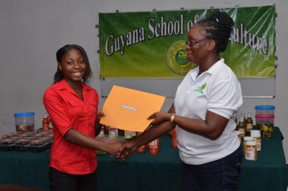 Kelshine Griffith receiving her certificate from Facilitator of the Agro-Processing Training Programme, Debra Paris