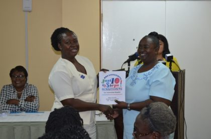 National Breastfeeding Co-ordinator, Ninian Blair presents report to representative of the New Amsterdam Hospital