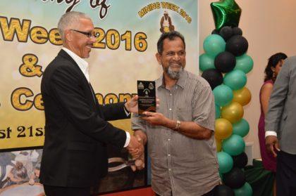 Minister of Business, Mr. Dominic Gaskin, presents the Top Dealer Award to Mr. Mohamed of Mohamed's Enterprise