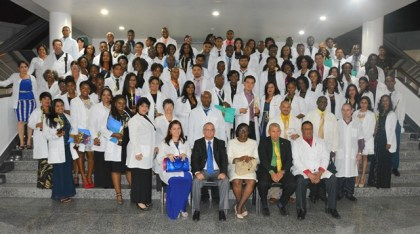 Minister of Public Health, Dr. George Norton, Minister within the Ministry of Public Health, Dr. Karen Cummings and Cuban Ambassador to Guyana, Mr. Julio César González Marchante pose with the 86 graduates as well and teachers of the 2016 Guyana/Cuba Medical Scholarship Programme