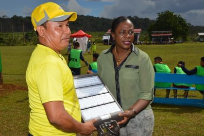 Minister within the Ministry of Education, Ms. Nicolette Henry officially hands over the floodlights to a member of the District Sports Council.