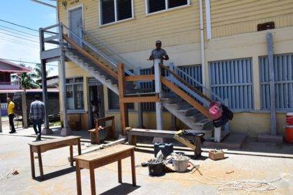 Workers renovating the stairway of the Lower Corentyne Secondary school