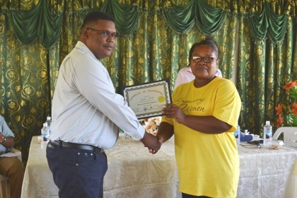 Regional Chairman, Mr. Brentnol Ashley presents a certificate to business owner Ms. Sophia Shelto.