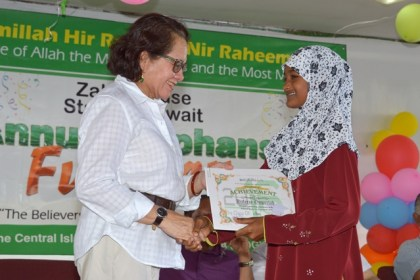 First Lady, Mrs. Sandra Granger presents a bursary certificate to Ms. Wafeeza Ompertab at the CIOG's Orphans and Vulnerable Children's Fun Day event.