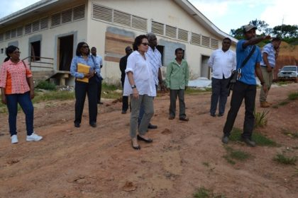 A worker directs First Lady, Mrs. Sandra Granger to the spot where a wheelchair ramp will be built to facilitate easy ingress and egress from the waiting area of the new hospital at Port Kaituma.