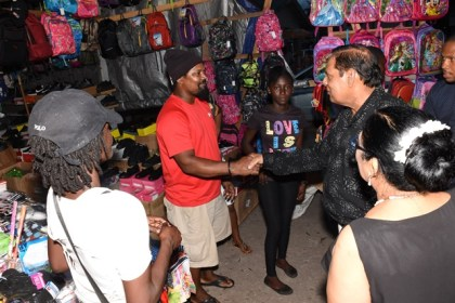 Prime Minister Moses Nagamootoo greets a vendor during his walkabout at the McKenzie Market