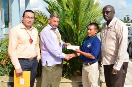 Minister of Indigenous Peoples' Affairs, Sydney Allicock (second left) handing over cheque worth $1.5M to Toshao, Marcus Alexander of Katoonarib, Region Nine