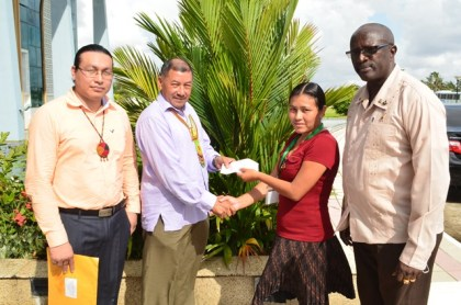 Minister of Indigenous Peoples' Affairs, Sydney Allicock (second left) handing over cheque worth $1M to Toshao, Vanica Edwin of Rukumoto, Region Nine