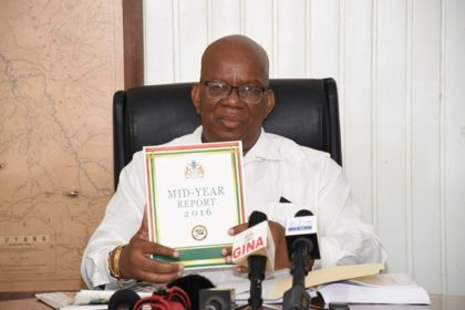 Minister of Finance, Winston Jordan displaying a copy of the Half- Year report