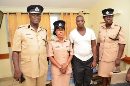 Assistant Commissioner of Operations Christopher Griffith, Deputy Superintendent of Police and Welfare Officer of the GPF Loreine Saul and DSM Maxine Graham  with Victor Faucette in his hospital room.