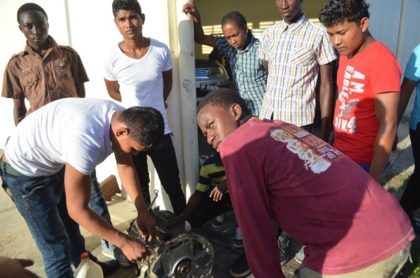 Some of the youths actively engaging in the Auto Mechanic class