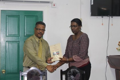 Chief Labour Officer of the Ministry of Social Protection, Charles Ogle handing over the report of the investigation into the death of Owen Morris, to the Human Resources Personnel of John Fernandes Limited, Donna Roberts-Benjamin