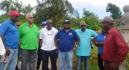 Minister Holder, Permanent Secretary of teh Ministry of Agriculture George Jervis, GLDA CEO and NAREI CEO and other officials while speaking to a farmer during the outreach