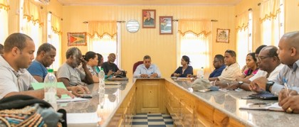 Presidential Adviser on the Environment, Rear Admiral (rtd) Gary Best, at the left of Regional Chairman, Mr. Gordon Bradford (centre), briefing regional officials on projects to be executed under the ,Green Bartica' programme.