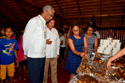 President David Granger and Minister of Indigenous People's Affairs, Mr. Sydney Allicock checking out some of the Indigenous delicacies served after the service