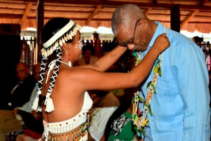 An Indigenous girl garlands President David Granger at the National Exhibition Centre at the launch of Indigenous Heritage Month.