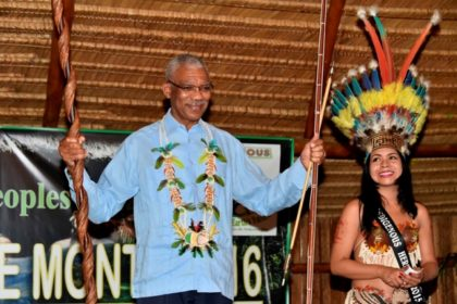 President Granger shows off his gifts, which were presented by the Indigenous people