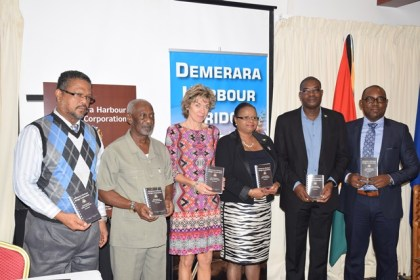 (From right to left) General Manager, DHBC, Rawlston Adams, Minister of Public Infrastructure, David Patterson, Minister of Social Protection, Volda Lawrence, Director Work Team, ILO, Claudia Coenjaerts, Minister within the Ministry of Social Protection, Keith Scott,  and Chief Labour Officer, Charles Ogle posing with their copy of the OS&H handbook