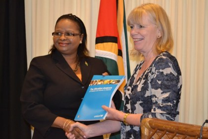 Minister of Social Protection Ms. Volda Lawrence receiving her copy of the Situation Analysis Report of Women and Children from UNICEF Representative to Guyana and Suriname, Ms. Marianne Flach.