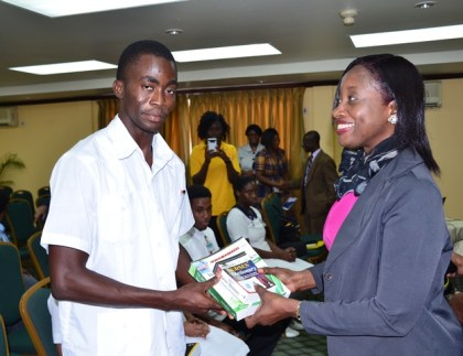 Director of Regional Health Services, Ministry of Public Health, Dr. Kay Shako hands over learning materials to a student nurse