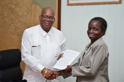 Minister of Finance, Winston Jordan hands over a debenture note to General Manager of the National Insurance Scheme, Doreen Nelson at the Ministry of Finance, Main and Urquhart Streets, Georgetown.