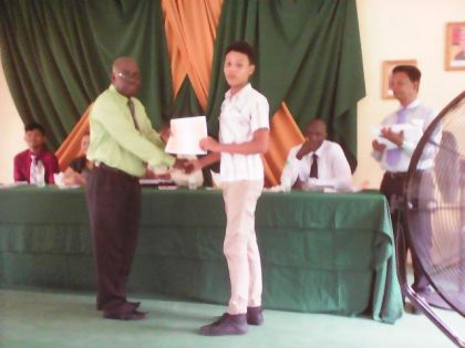 Mr. Saul presents certificate of participation to youth participant,Mr. Jaleel Huntley from Bartica.