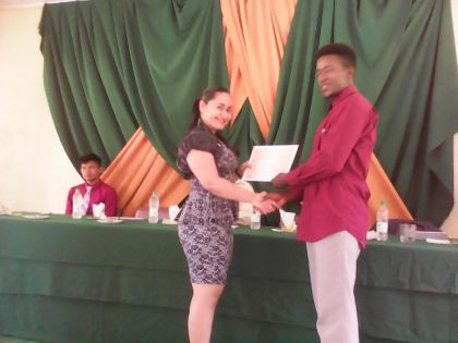 Ms. Adeti de Jesus, Senior Research and Planning Officer, PAYEU presents certificate of participation to youth participant, Mr. Lorenzo Bess who is a teacher at Three Miles Secondary, Bartica.