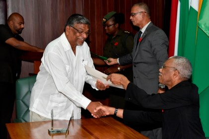 President David Granger presents the Instrument of Appointment to former Minister of Labour, Mr. Nanda Kishore Gopaul.