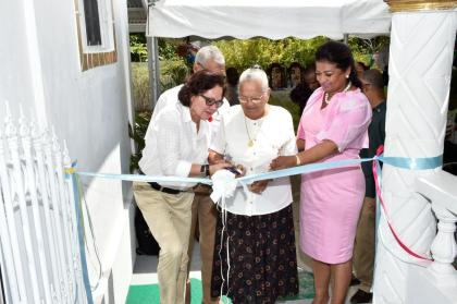 President David Granger (partly hidden behind the First Lady) First Lady, Mrs. Sandra Granger and Mrs. Supriya Singh-Bodden help Mrs. Seraji Sankar to cut the ribbon to officially open the Guyana Foundation Sunrise Centre at Zorg-En-Vlygt, Essequibo Coast
