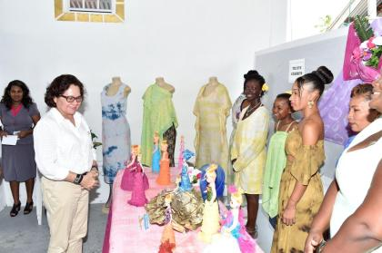 First Lady, Mrs. Sandra Granger admires some of the decorative dolls created by participants in one of the Sunrise Centre's skills training programmes, while some of the representatives display clothing made from tie dye and batik designing techniques