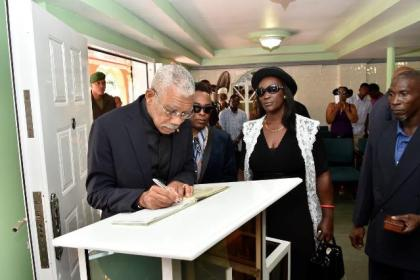 President David Granger signs the Book of Condolence at the viewing ceremony for the late Mr. Malcolm Corrica, at the Sandy's Funeral Home.