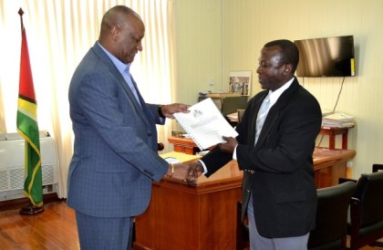Brigadier (Ret'd) Edward Collins, Commissioner of the Commission of Inquiry, handing over the Preliminary Report to Minister of State, Mr. Joseph Harmon, earlier today.