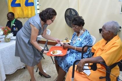 First Lady, Mrs Sandra Granger serves Past President of the SANRIC Senior Citizens' Group Sister Joyce Butts as Sister Dorris Williams look on