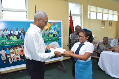 President David Granger presenting Ms. Jeanelle Fredericks with her bursary award. Ms. Fredericks, who hails from Upper Takutu-Upper Essequibo (Region Nine) is from the 2012 batch of awardees. She is now a fifth form student at the St. Joseph's High School