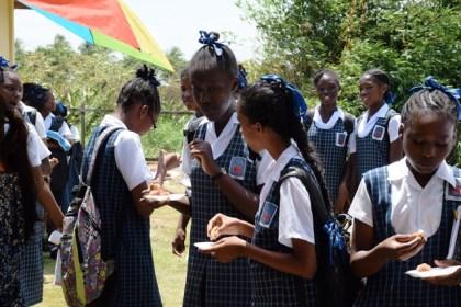 Students enjoying samples of fried tilapia and tambaki (fresh water pakoo) at the Satyadeo Sawh Aquaculture Station, Mon Repos