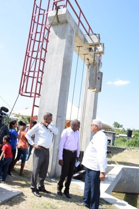 Minister of Agriculture Noel Holder and other officials taking a look at the newly commissioned sluice