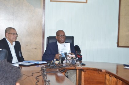 Hon. Minister of Finance, Winston Jordan displaying a copy of the  Medium Term Debt Report which was laid before cabinet