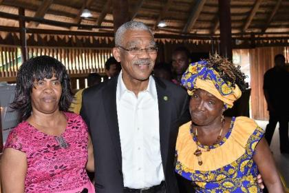 President David Granger shares a photo moment with two of the attendees at today's event, who hailed from Linden.