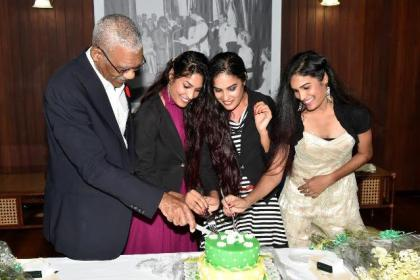 President David Granger sticks the birthday cake with Ms. Radha Mansaram, Ms. Rajshri Mansaram and Ms. Reenica Mansaram on their 22nd birthday.