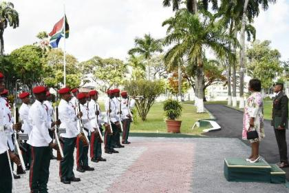 High Commissioner of the Republic of South Africa, Her Excellency Xoliswa Nomathamsanqa Ngwevela stands at attention during a ceremonial flag raising at State House, before presenting her Letters of Credence to President Granger