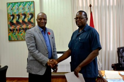 Minister of State, Mr. Joseph Harmon shakes hands with the Commissioner of the newly established Board of Inquiry, Mr. Winston Cosbert, who has been tasked with probing into allegations of malpractices in the procurement division of the Ministry of Public Health