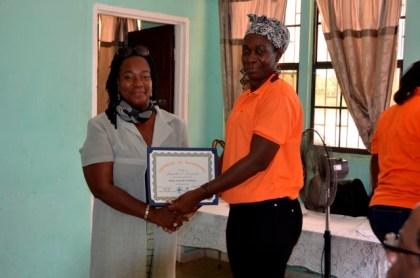 Business entrepreneur, Ms. Dolerise South presents a certificate to Ms. Jacqueline Fernandes of Yarrowkabra.