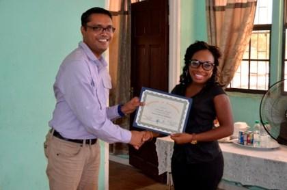 Facilitator of Interweave Solutions, Mr. Sanjay Pooran presents a certificate to Ms. Amanda Joseph, who operates a salon in Kuru Kururu.