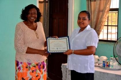 Regional Chairperson, Demerara-Mahaica (Region Four), Ms. Genevieve Allen presents a certificate to Ms. Rosalind Persaud also of Kuru Kururu, a small business owner.