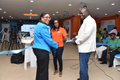 Minister of Public Telecommunications, Catherine Hughes, CEO of GTT Justin Nedd and Manager of the 'Customer Experience Store' on Brickdam cut the symbolic ribbon