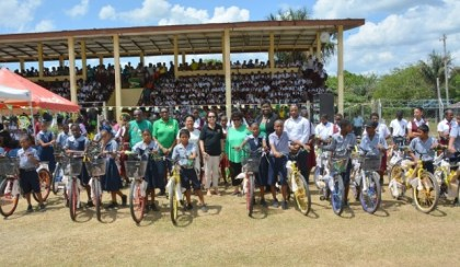 Students from several schools in Kwakwani display their brand new bicycles along with Minister of Social Cohesion, Ms. Amna Ally, First Lady, Mrs. Sandra Granger and representatives of Region Ten.