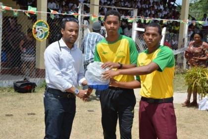 Mr. Jermaine Figueira, Member of Parliament, presents a quantity of sporting gear to members of one of the sports club in Kwakwani Upper Demerara-Berbice (Region 10).