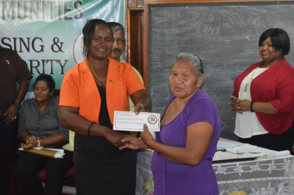 A Regional Official of Region Two hands over a Home Improvement Subsidy to one of the beneficiaries