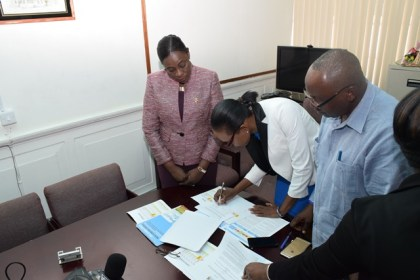 Minister within the Ministry of Education, Nicolette Henry along with Ava Marie Lindie of Alpha and Omega Community Health Associates signing the grant and Trevor Thomas, board member of Global Fund